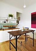 Vintage, industrial-style table and stool in front of white kitchen counter and narrow crockery shelves