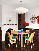 Pale, wooden dining set with turquoise seat cushions in front of dark wine rack and sideboard; colourful artworks on walls