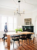 Simple metal chandelier above modern wooden table and black chairs in dining room with marquetry parquet floor and stucco ceiling