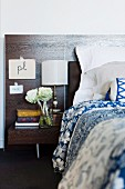 Bed with blue and white bed linen, bedside cabinet and dark wood headboard; calligraphy on paper taped to headboard, vase of flowers and antique lamp