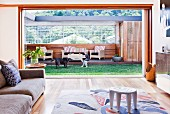 View across sofa and patterned rug through open sliding doors of table and chairs on roofed outdoor living room