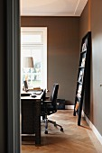 Desk and magazine rack leaning against wall in home office space with grey-painted walls