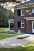 Two-storey villa with brick facade and veranda in garden