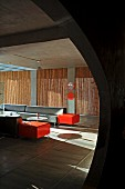 View though rounded opening into minimalist lounge area with grey and orange sofa set; screens of bamboo poles in windows in background