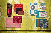 Samples of various floral fabrics in shades of red and blue on gold background
