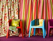 Scatter cushions and fabrics on colourful shell chairs; draped bolts of striped and floral fabrics in background