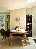 Dining area with black designer chairs around wooden table; sunburst clock on wall