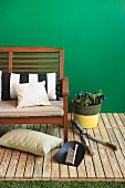 Potted plant next to garden bench and various gardening tools arranged on wooden decking against green-painted wall