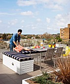 Bench with striped seat cushion, table and chairs on roof terrace; man arranging cushions