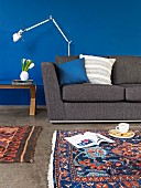 Dark grey sofa, designer standard lamp and patterned, Oriental rug in front of wall painted a rich blue