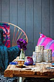 Moroccan silver lanterns and mocha cup on rustic wooden table; colourful scatter cushions and wood cladding in background