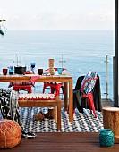 Holzbank, gedeckter Tisch und rote Retrostühle auf Terrasse mit Meerblick durch transparente Glasbrüstung