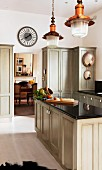Country-house kitchen with pale grey cupboards; open doorway in background with view into living room beyond