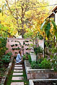 Woman next to raised bed with stone wall in autumnal garden