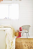Vintage rattan chair next to bed with floral blanket against white, wooden wall and window with airy curtain