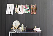 Place mats with various motifs hanging on washing line against wooden wall painted dark grey; crockery on table below