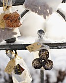 Small bags of biscuits hanging on snowy fence as Advent calender