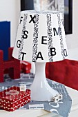 White table lamp decorated with black letters and washi tape