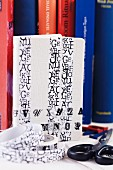 White notebook decorated with washi tape with pattern of letters