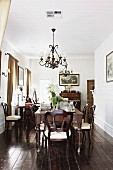 Dining table, antique chairs, wrought iron chandelier and dark wooden floor in traditional, elegant dining room