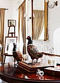Stuffed pheasants on table between antique boxes, gilt-framed mirrors and elegant easel