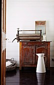 White metal water jug on dark wooden floor in front of old mangle on top of antique wooden cabinet