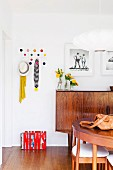 Wooden fifties sideboard, classic Hang-It-All coat rack next to black and white photos on wall and dining set in foreground