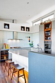 Kitchen island with blue, half-height wall and wooden stools in corner of open-plan kitchen with transom windows
