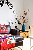 Colourful ethnic blanket on leather sofa, plant arrangement on side table in corner and objets d'art on wall