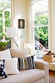 Corner of sunny room with two windows and pale, timeless sofa