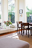 Antique table in corner of sunny dining area with multiple windows and low, broad windowsill