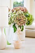 Fensterbank-Deko mit Vasen, Hortensienblüten und einem Schälchen mit Griff in Form eines stilisierten Elchkopfs