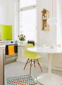 Mixture of classic furnishings in kitchen - white tulip table and green shell chair in white kitchen
