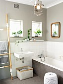 Renovated bathroom - sink and bathtub against half-height tiled wall below walls painted pale grey