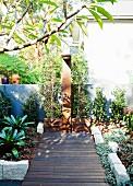 Wooden deck leading to outdoor shower in urban garden
