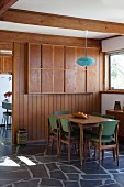 Pendant lamp with blue lampshade above 50s-style dining set in dining room with wooden partition wall and stone-flagged floor