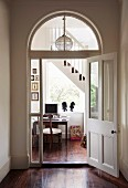 Foyer in grand house with view through arched doorway into stairwell with desk below window