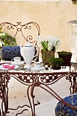 Tea service and potted plants on metal table with glass top