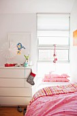 Bed with pink bed linen below window and Christmas stocking hung on white chest of drawers in girl's bedroom