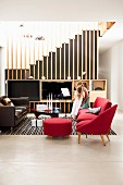 Red armchair with footstool and sofa in open-plan living area; media cabinet against staircase with floor-to-ceiling wooden slats as see-through partition