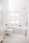 White bathroom with bathtub and mosaic tiles on floor