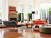 Seating in various colours, coffee table and open fireplace in corner of high-ceilinged, bright interior