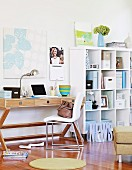 Chair with white upholstery in front of wooden desk next to white shelves of office supplies