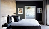 Modern bed with upholstered frame and scatter cushions against matt, varnished wooden wall; wall painted dark grey with doorway leading to ensuite bathroom in background
