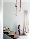 Pendant lamps above modern interior staircase made from steel girders with floating wooden treads and glass balustrade; girl in background