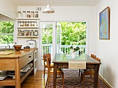 Rustic dining area and counter with shelving in base unit in simple dining room with open balcony door