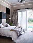 Double bed against wall with panels in various shades in traditional interior; open terrace door with view of pool
