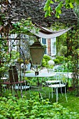 A white-painted metal table and garden chairs for sale with an antique lantern under a wicker pergola