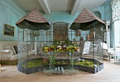Antique bird aviaries and wire shelves with garden ornaments in front of upholstered furniture all for sale in an old French country house