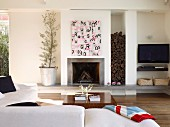 View across corner sofa to modern chimney breast with stacked firewood to one side and TV in niche
